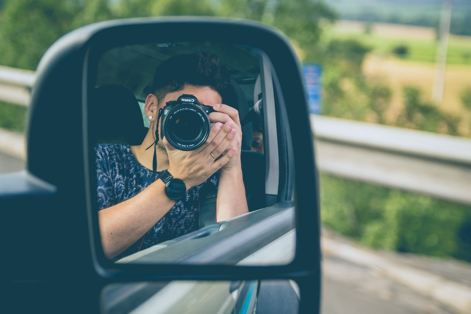 man-taking-picture-in-sideview-mirror.