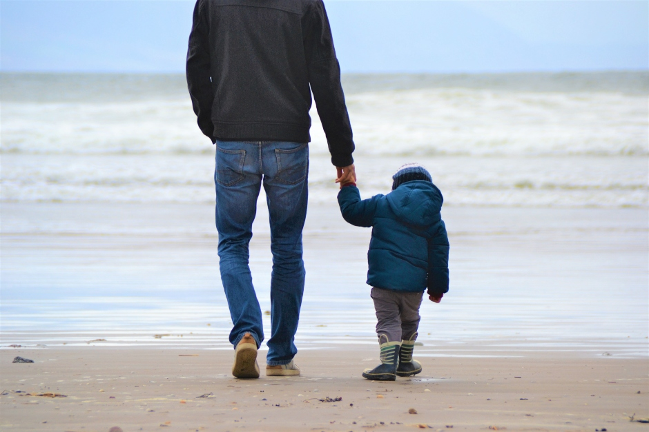father-holding-child-hand-on-beach-in-winter