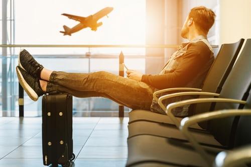 Man sitting in airport watching plane take off