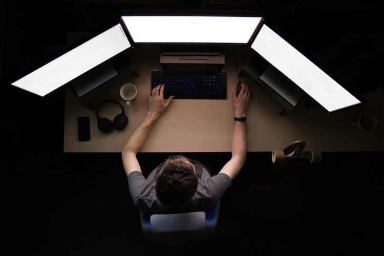 Man sitting at three computer monitors